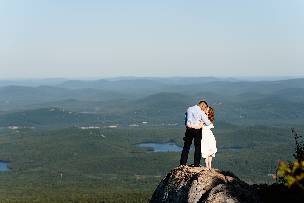 bride and groom kissing on summit of mount chocorua in new hampshire white mountains for adventure session