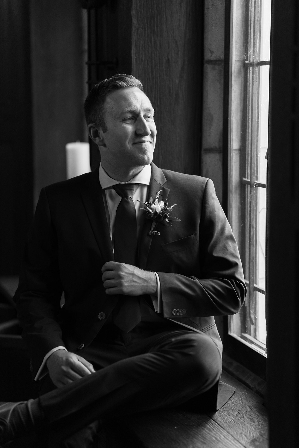 moody black and white photo of a groom looking out the window