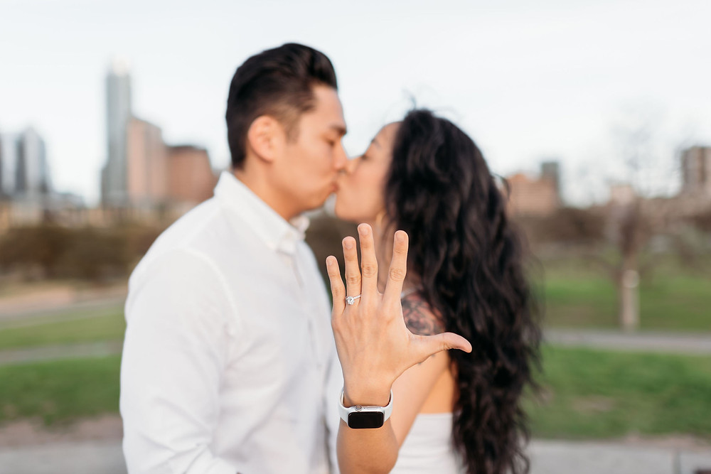 doug sahm hill downtown austin proposal. couple kisses while newly engaged bride shows the camera her left hand to show off her engagement ring. austin skyline in background.