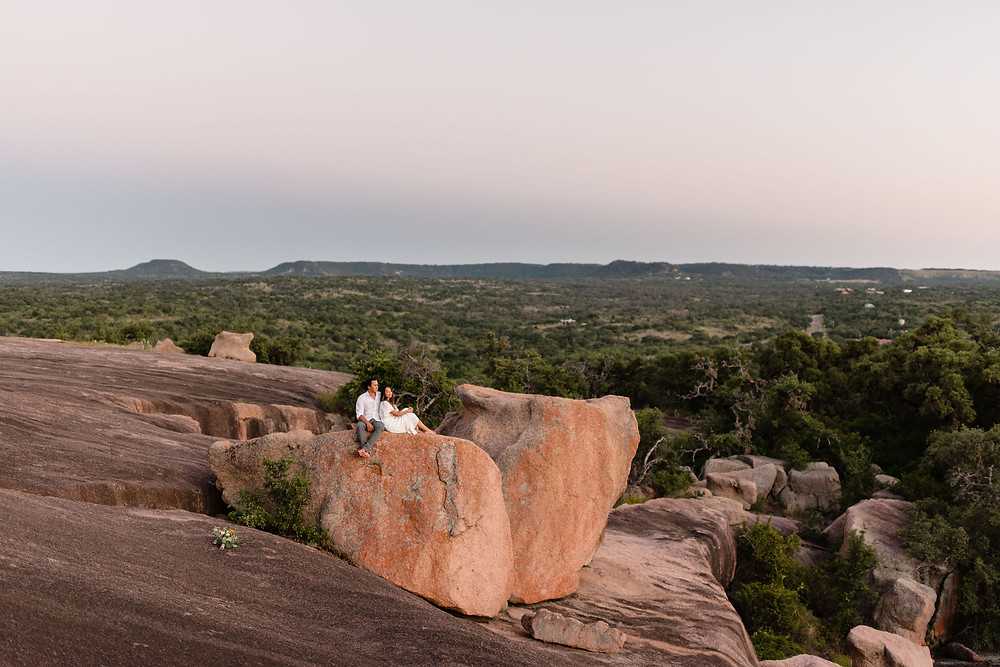 enchanted rock landscape. couple sits on a big rock overlooking the hill country beyond