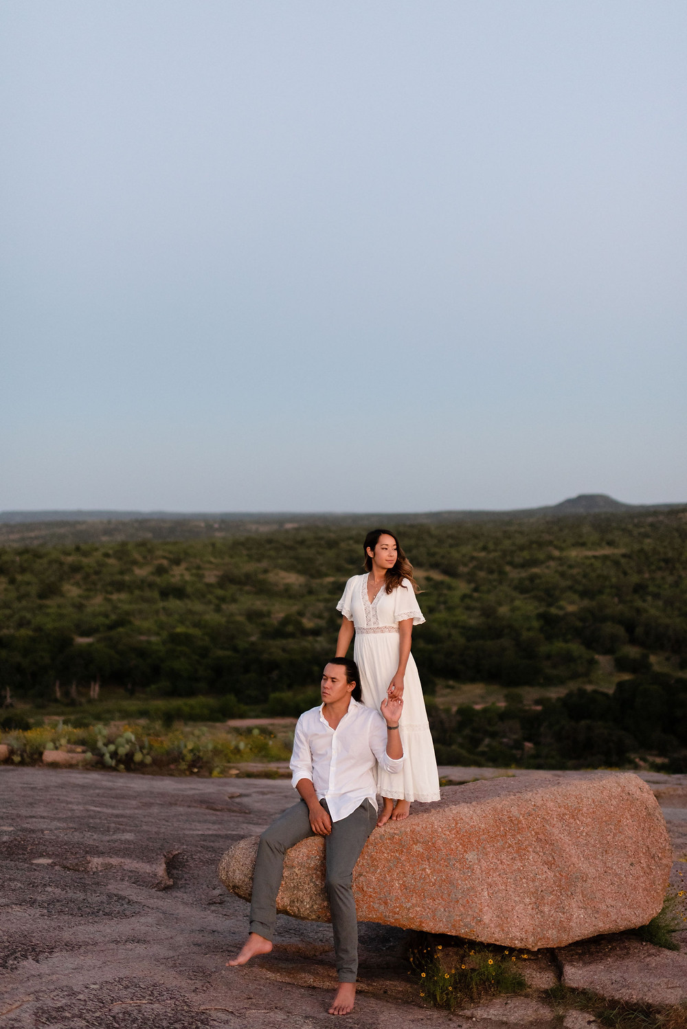 groom sits down on rock. bride stands on the same rock behind him. they look off in opposite directions.