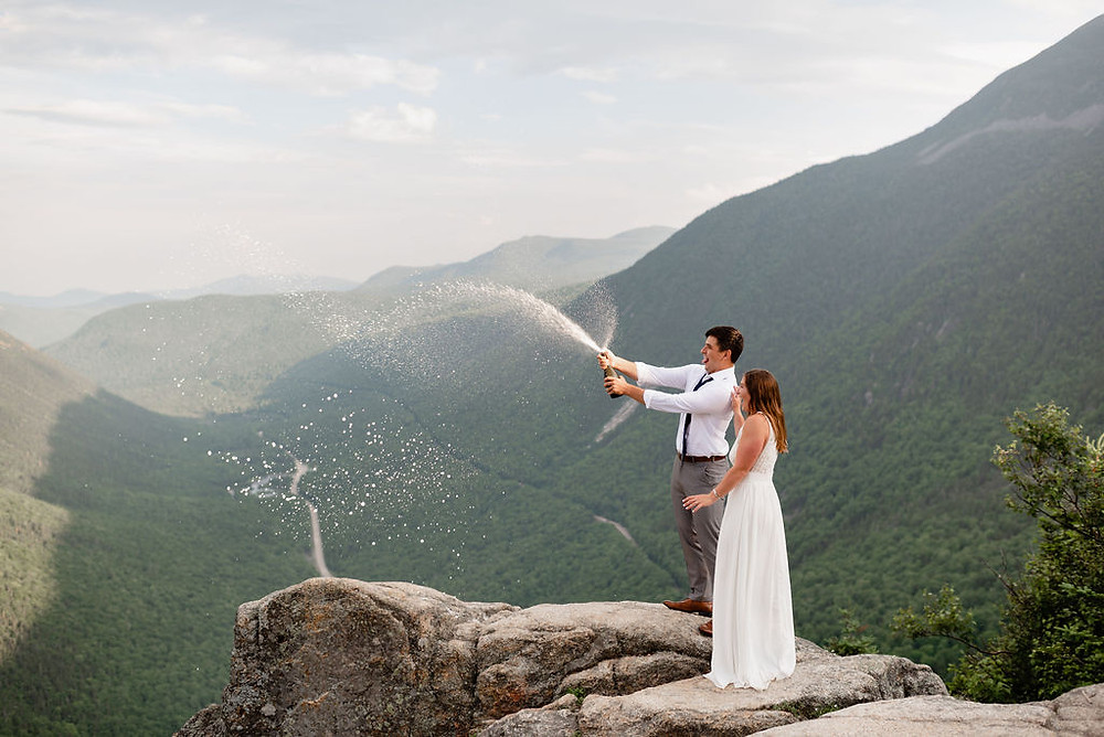 couple popping champagne for their elopement on mount willard