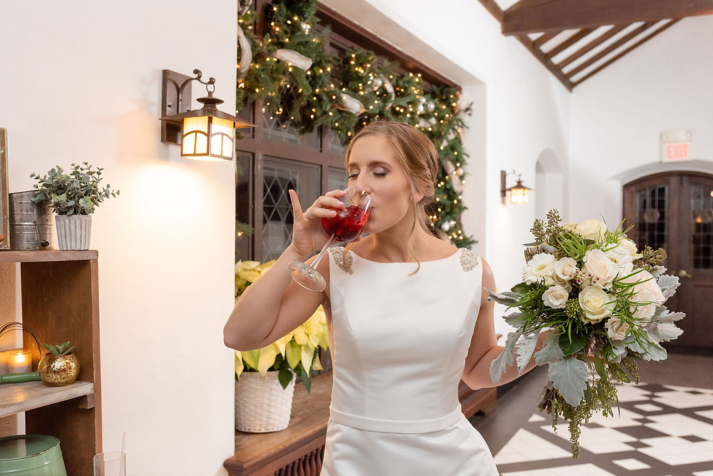 candid photo of bride drinking wine with her pinky up