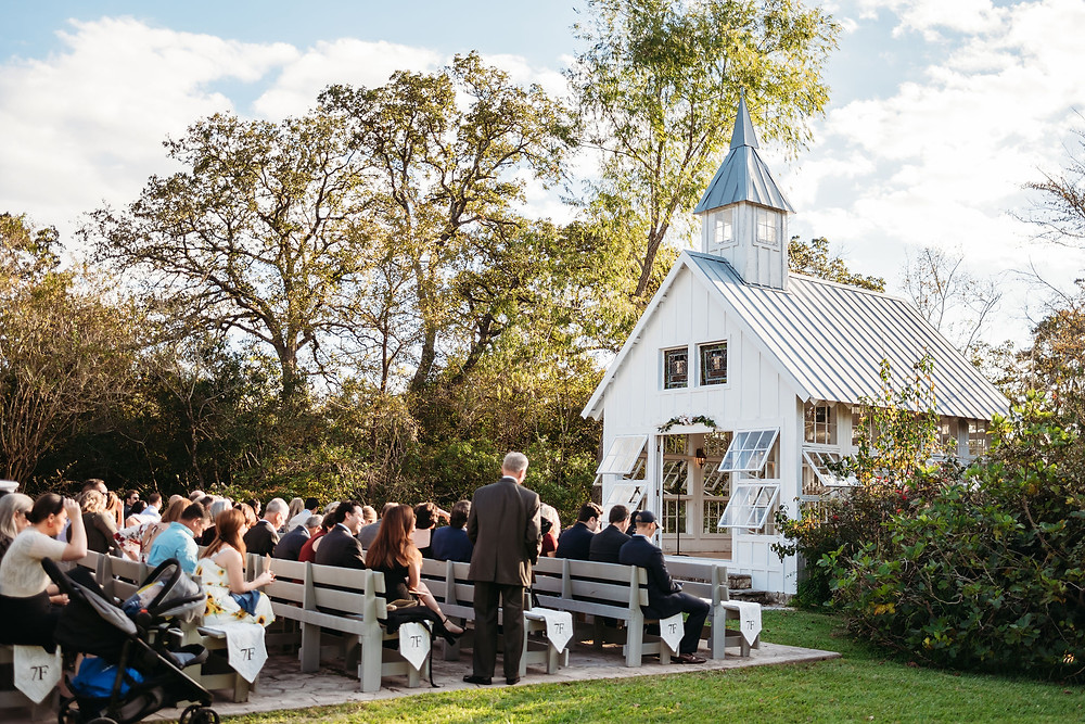 guests seated before outdoor ceremony at 7F lodge. It is a sunny day. Guests are seated on benches. There are trees and a white chapel.