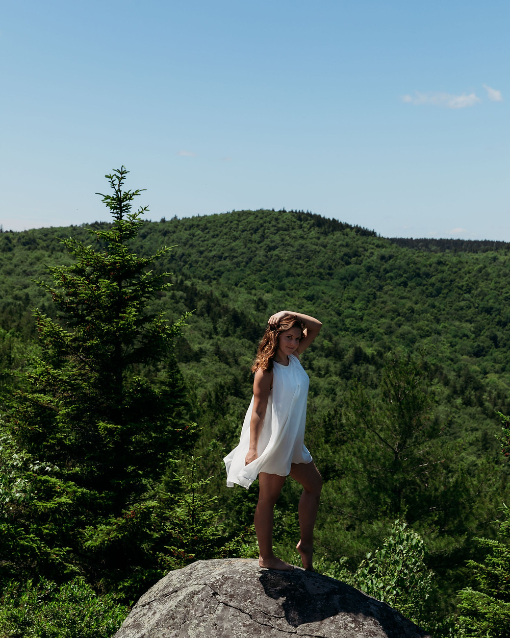 bride standing on mountain with hair and dress blowing in wind for adventure elopement