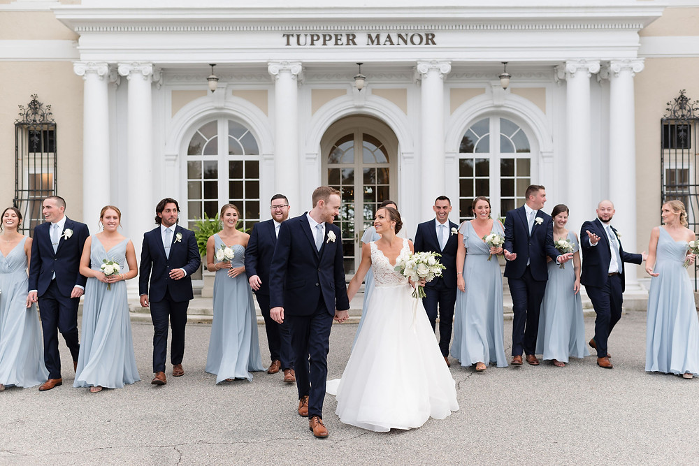 entire wedding party walking towards camera laughing outside the front entrance of Tupper Manor