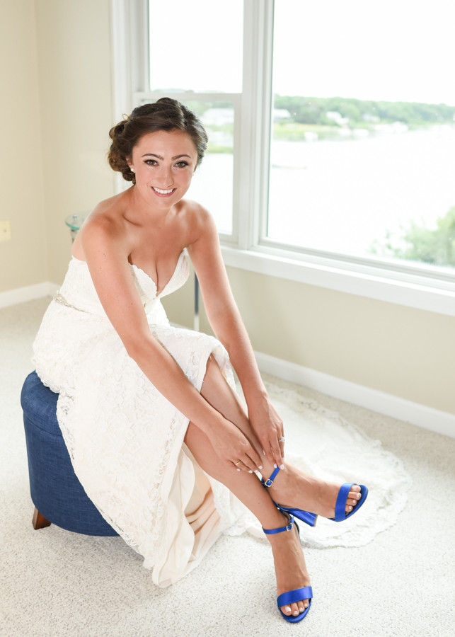 bride putting on blue wedding shoes