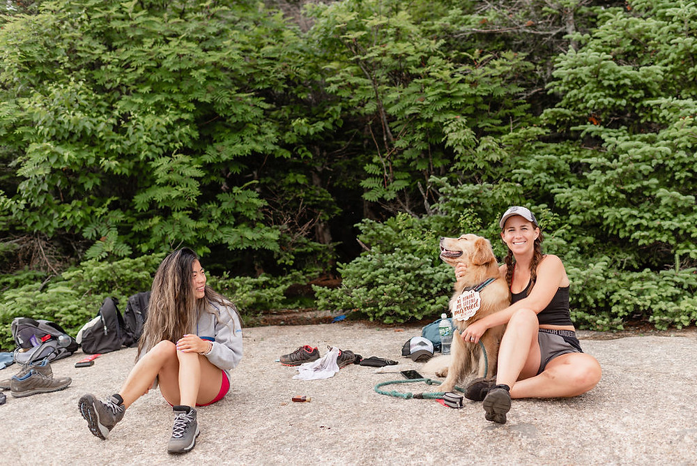 behind the scenes photo of two girl sitting with the couple's dog and belongings