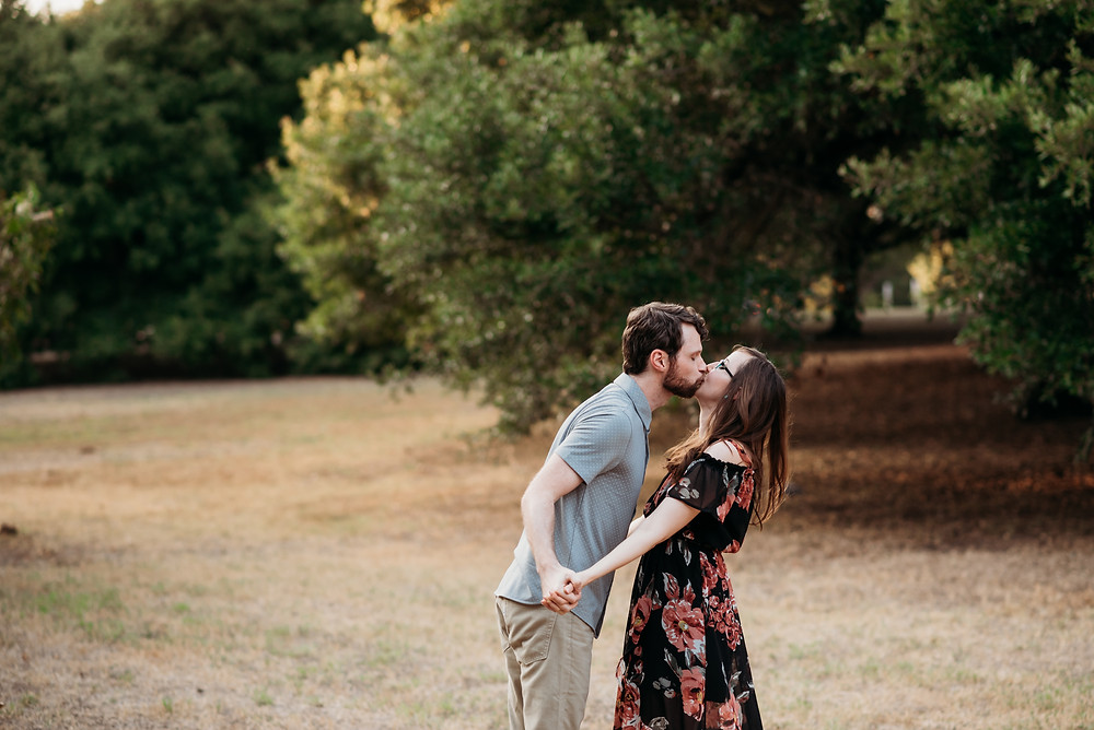 a couple is standing in a field holding hands, facing each other. they're kissing and it looks like the guy is exerting more force because the girl has a slight backbend.