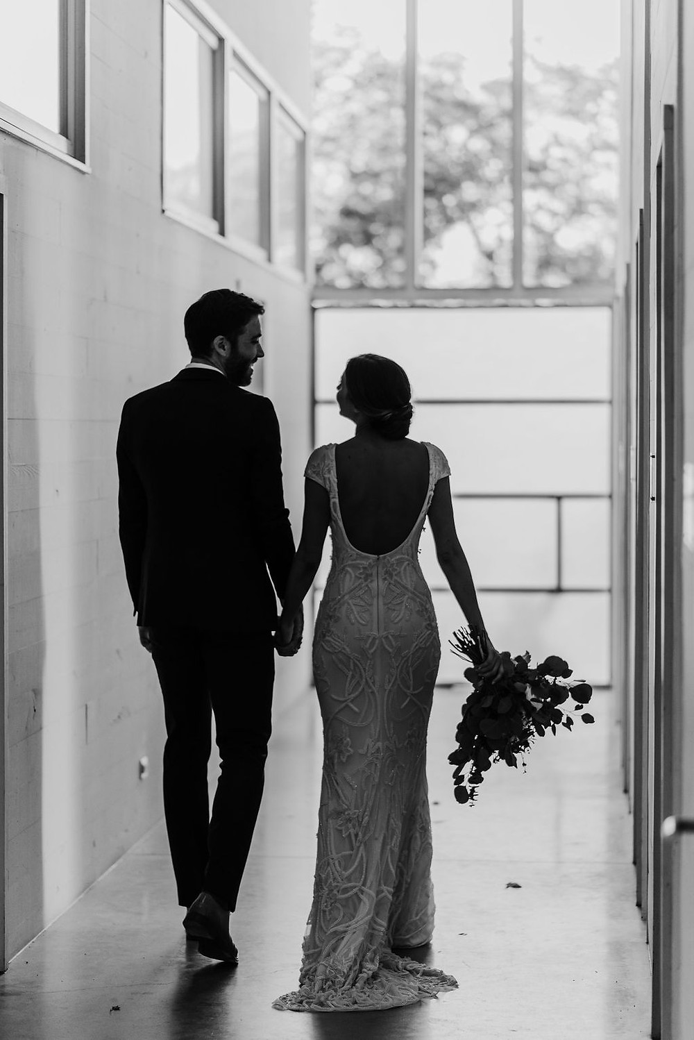 silhouette photo of bride and groom walking away from the camera in a hallway