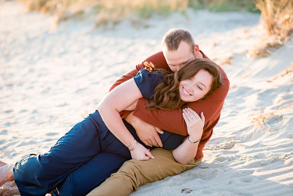 couple wrestling on beach for engagement photos at lighthouse inn in West Dennis Cape cod, MA