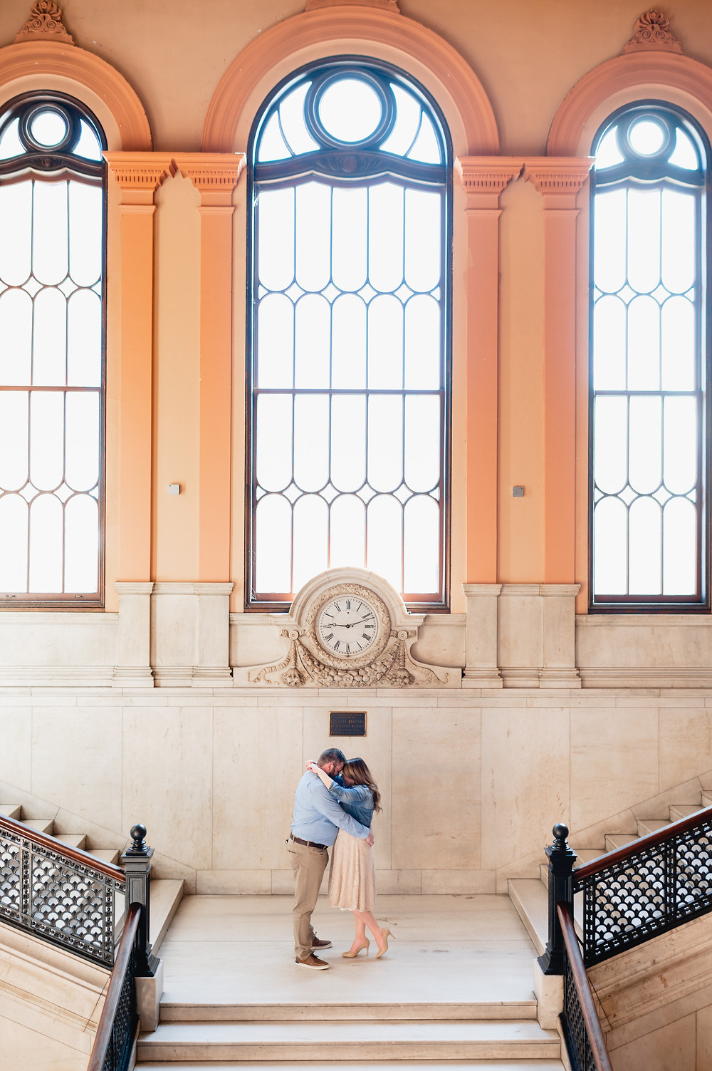 couple posing at top of staircase with large windows behind them