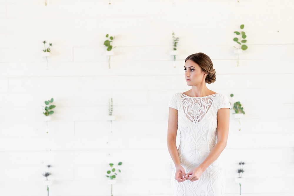 nervous bride in front of flower wall at prospect house