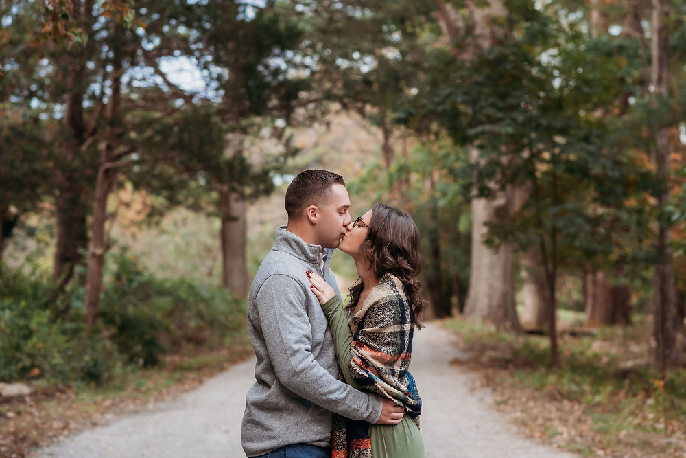 guy and girl stand in middle of street kissing with fall foliage on either side of them