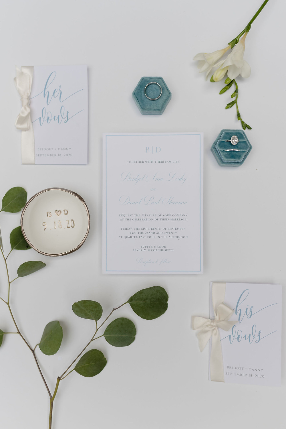 flat lay wedding details with invitations and wedding rings