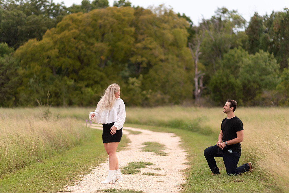 girl turns around to see her boyfriend down on one knee