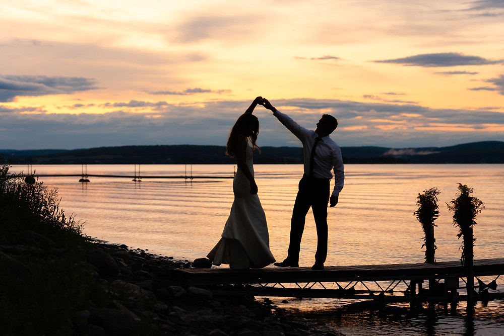 couple dancing on dock at sunset on coast of maine