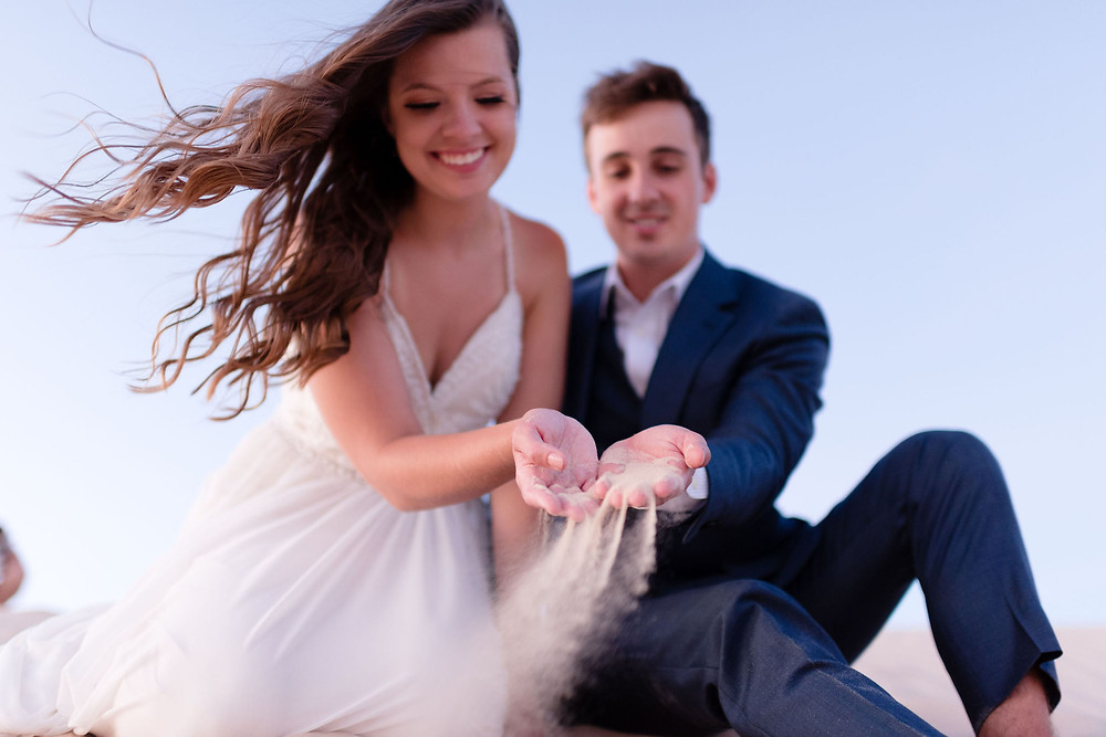 the couple performs a different kind of sand ceremony during their elopement. instead of pouring sand into beakers, they conjoin their fistsfull of sand and let it drop to the ground. the angle is from below, with the focus on the sand falling out of their hands. their faces are out of focus behind the hands