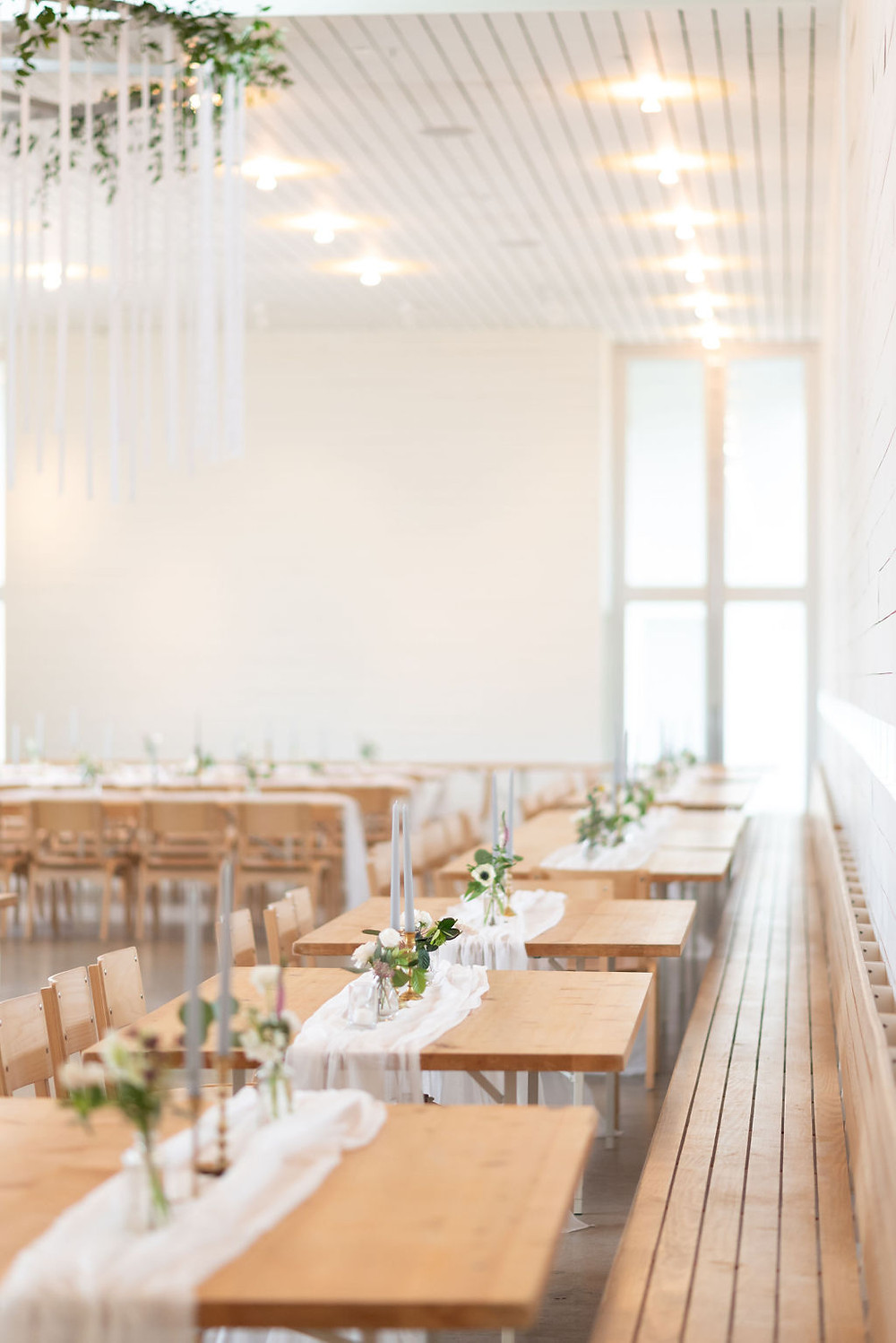 reception area detail shot. long wooden tables with a white chiffon table runner, gray candles, and little glass vases with small assortment of flowers. amazing natural light