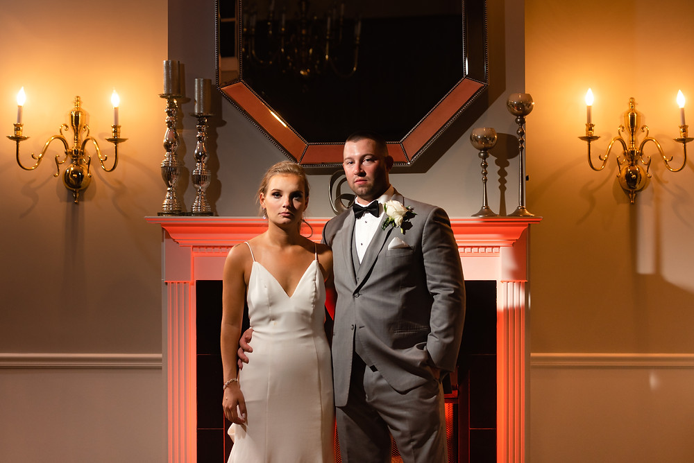 colored gel off camera flash lighting at a wedding. couple stands in front of fireplace that is illuminated in red flash