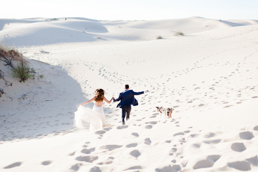 couple is holding hands while running down one of the sand hills with their dog away from the camera