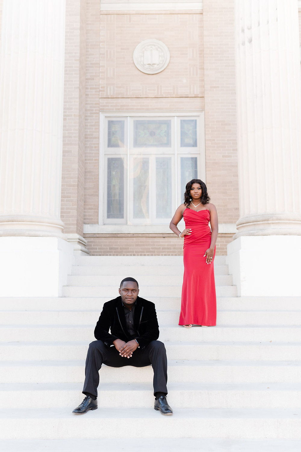 formal engagement session in downtown austin at first methodist united church . guy is sitting on the stairs, facing the camera. girl is standing on stairs a few stairs behind him with her hand on their hip. formal, serious engagement session pose. there are tall columns on either side of them