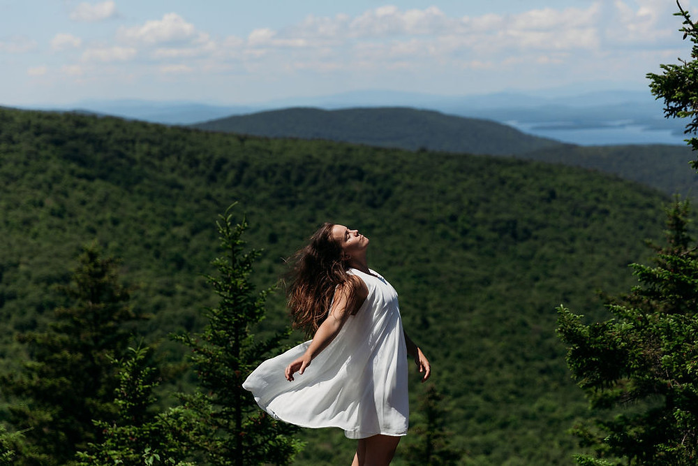 bride's dress blowing in the wind on top of a mountain in new england