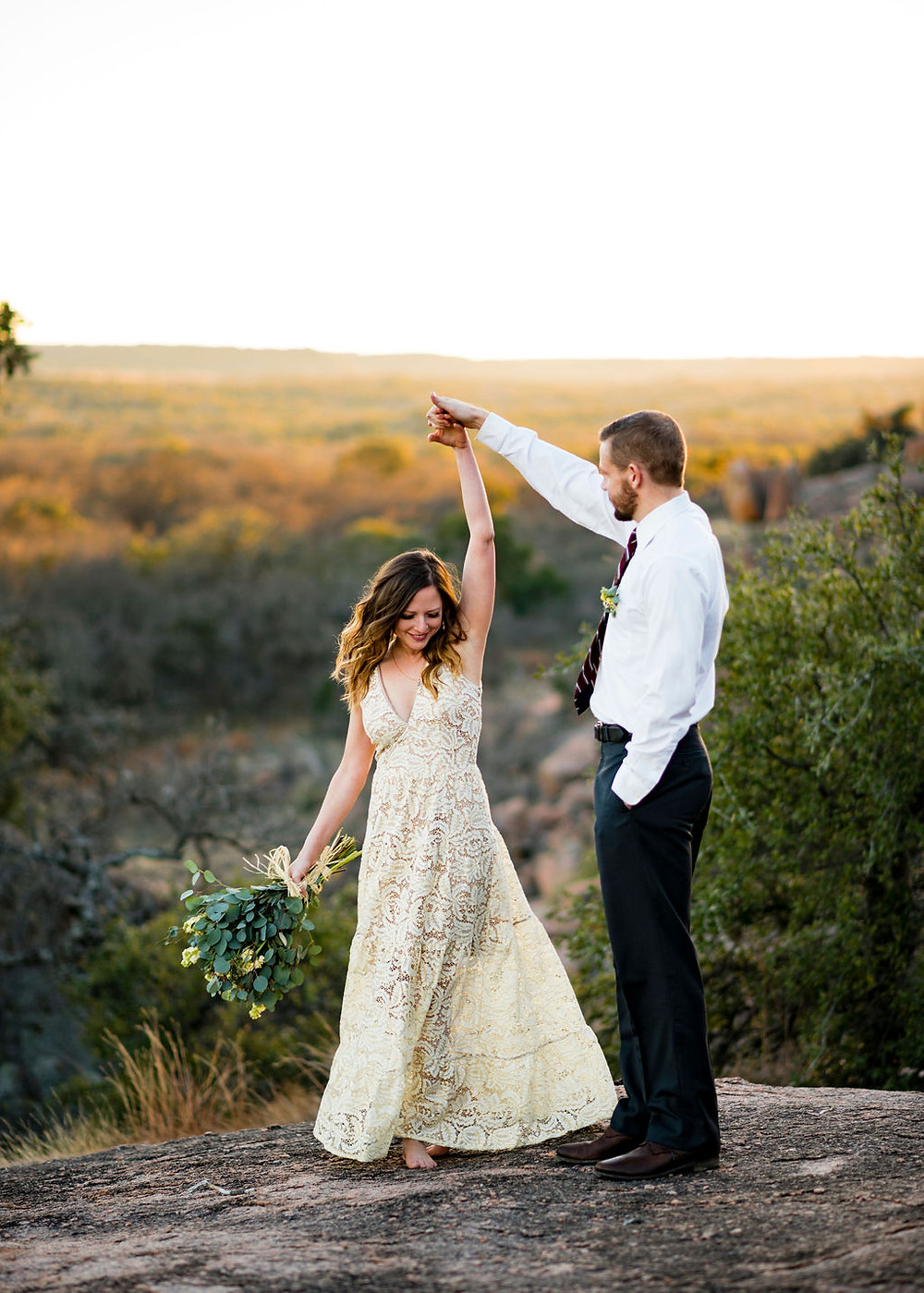 groom spins bride during first dance at their elopement. The bride's tan and white boho dress flairs out and she has a big smile. Bride is holding her bouquet in her free hand. In the background you can see the hill country during golden hour. The couple is on enchanted rock for their elopement.