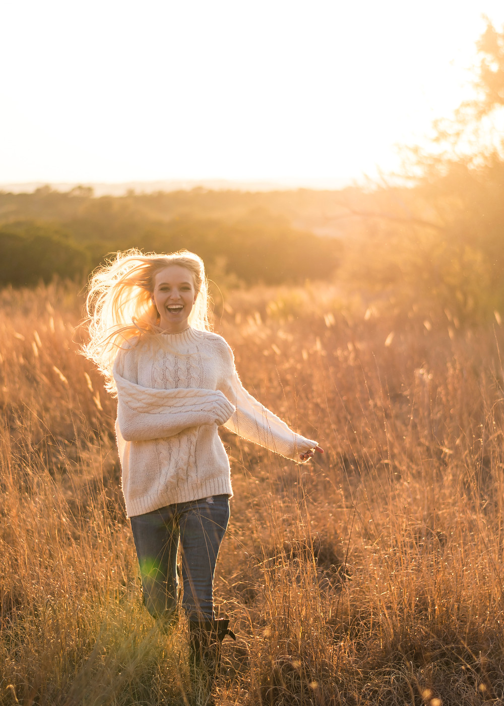 girl running through a field at sunset with light shining through her hair