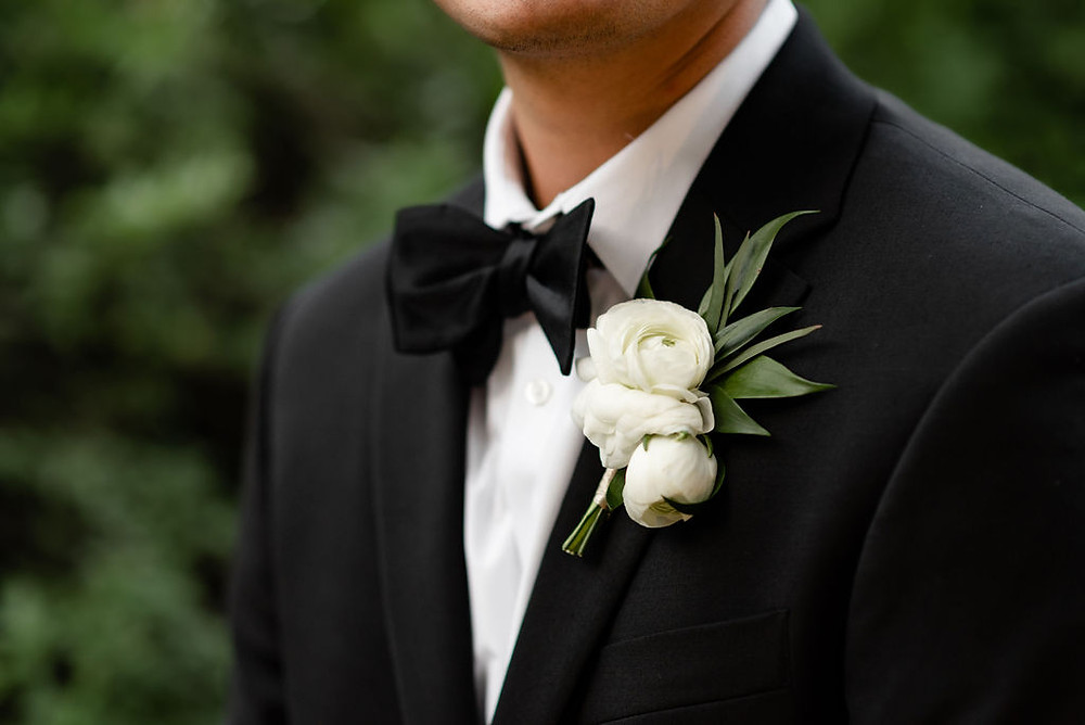 grooms portrait in the butterfly garden at villa antonia. close up detail photo of boutonnière and bowtie
