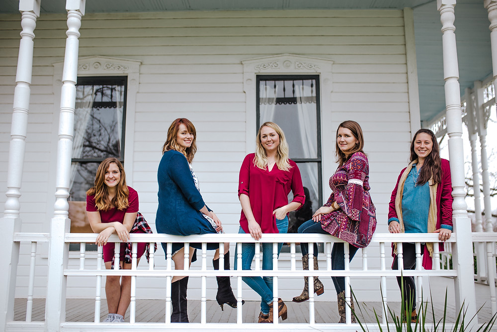 girls posing over a railing at barr mansion smiling at the camera