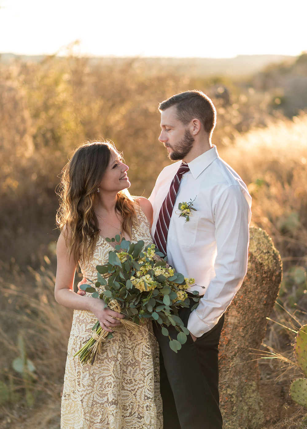 bride and groom look at each other and smile. Bride is holding bouquet with one hand. Their arms are wrapped around each other's backs. They are standing on enchanted rock for their elopement with the texas hill country in the background during golden hour