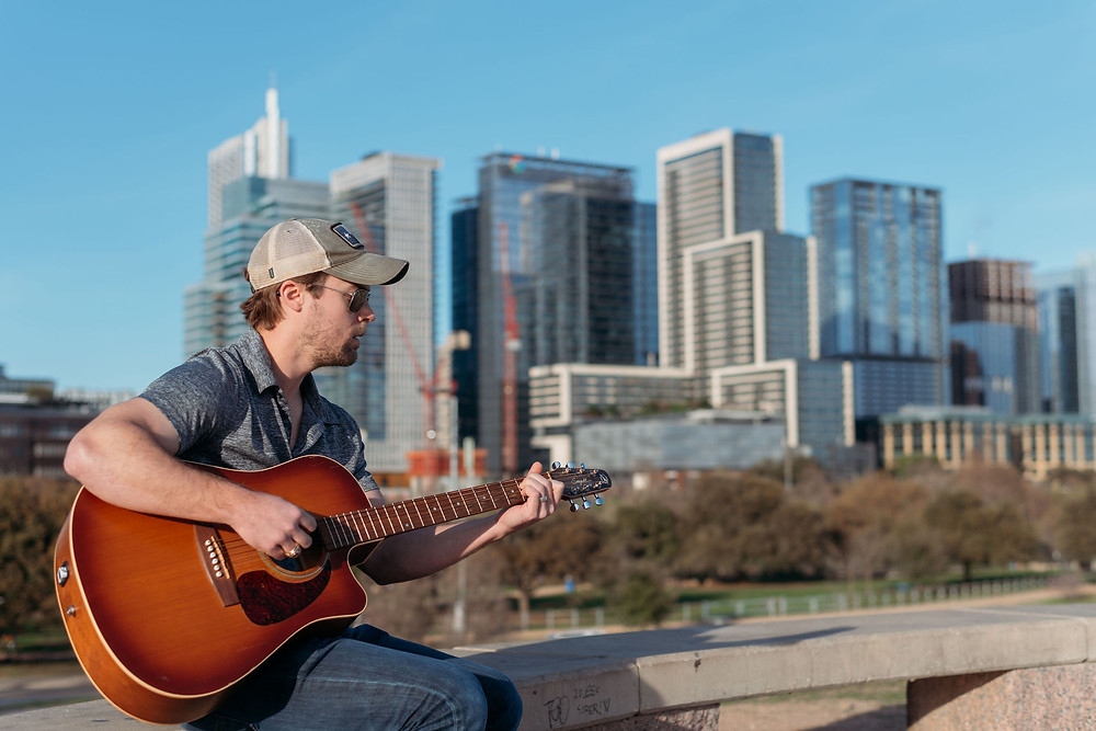 jeremy Mcbee playing guitar on doug sahm hill with austin skyline in background right before tamara merri photography photographs a couple's proposal