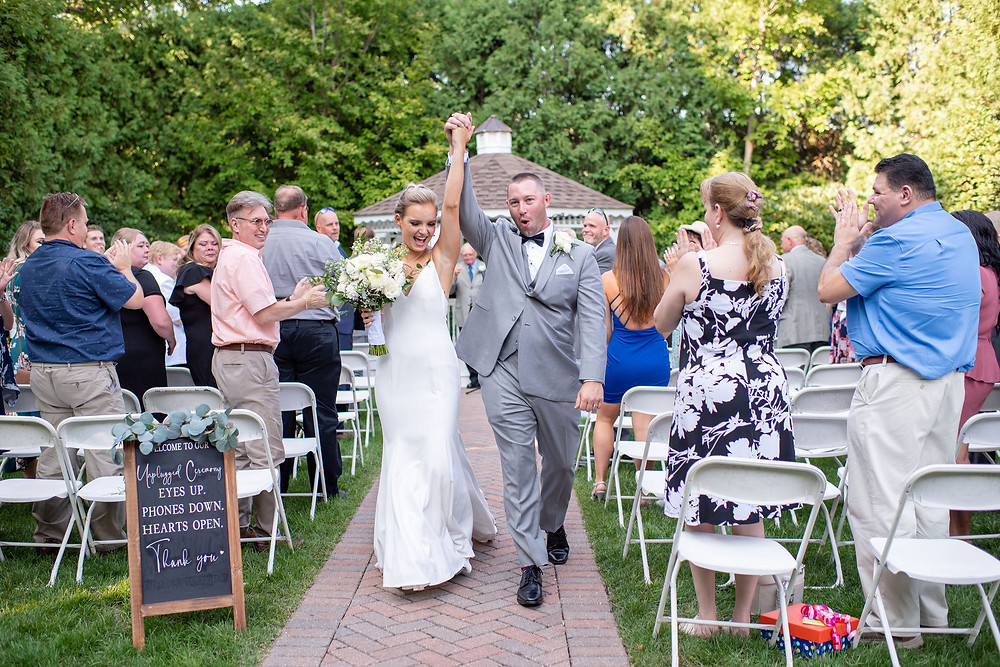 bride and groom celebrate walking down aisle after wedding ceremony
