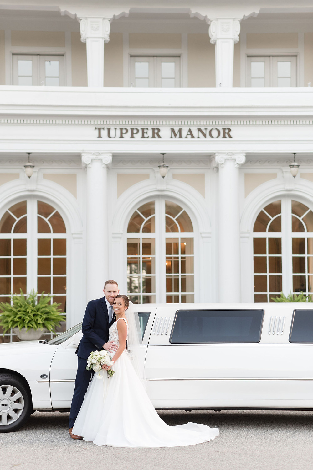 couple standing in front of tupper manor front entrance with white stretch limo