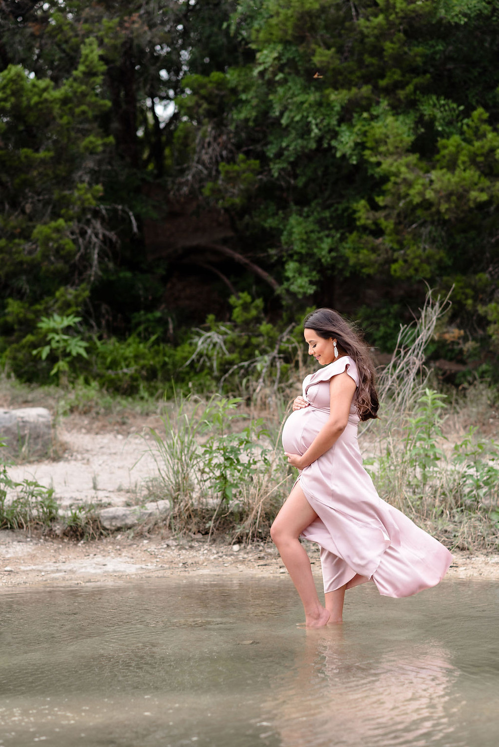 a pregnant woman stands in shallow water with her hands on either side of her baby bump. the wind is blowing which is causing her hair and dress to blow away from her in a very pretty, dramatic way.