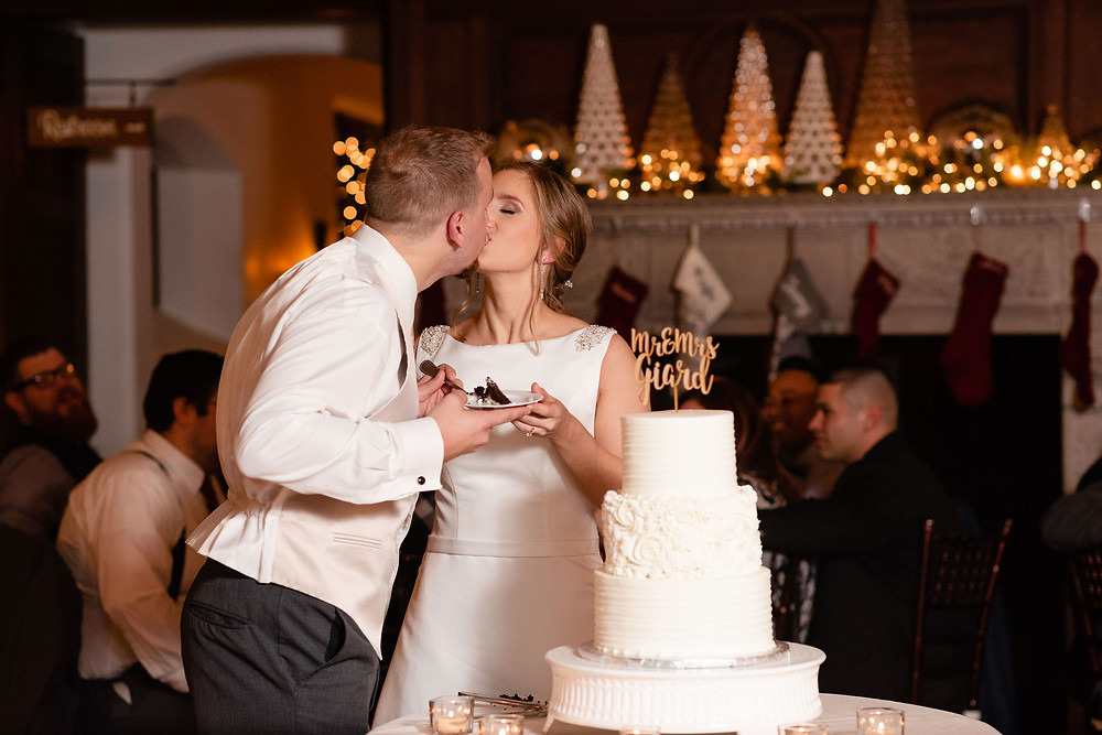bride and groom kiss after cutting their wedding cake