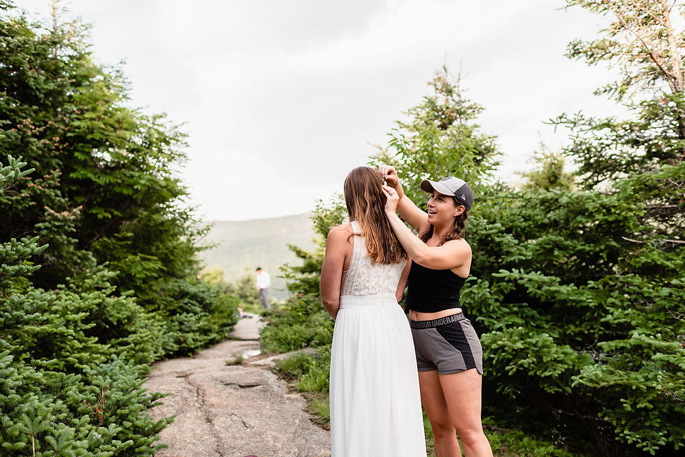maid of honor doing bride's hair surrounded by trees. you can see the groom off in the distance