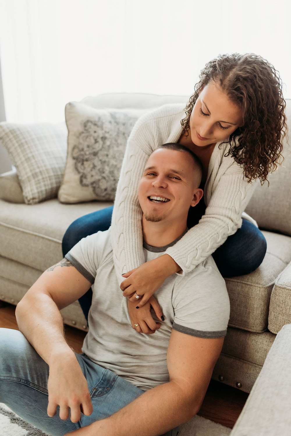 in home engagement session with couple posed in living room