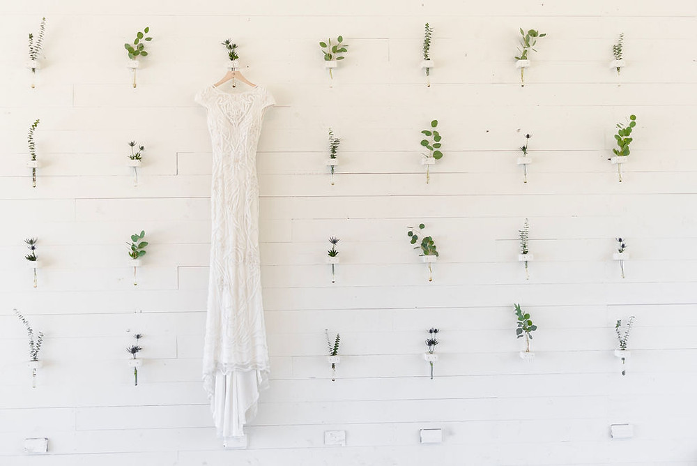 wedding dress hung up on the flower wall at prospect house