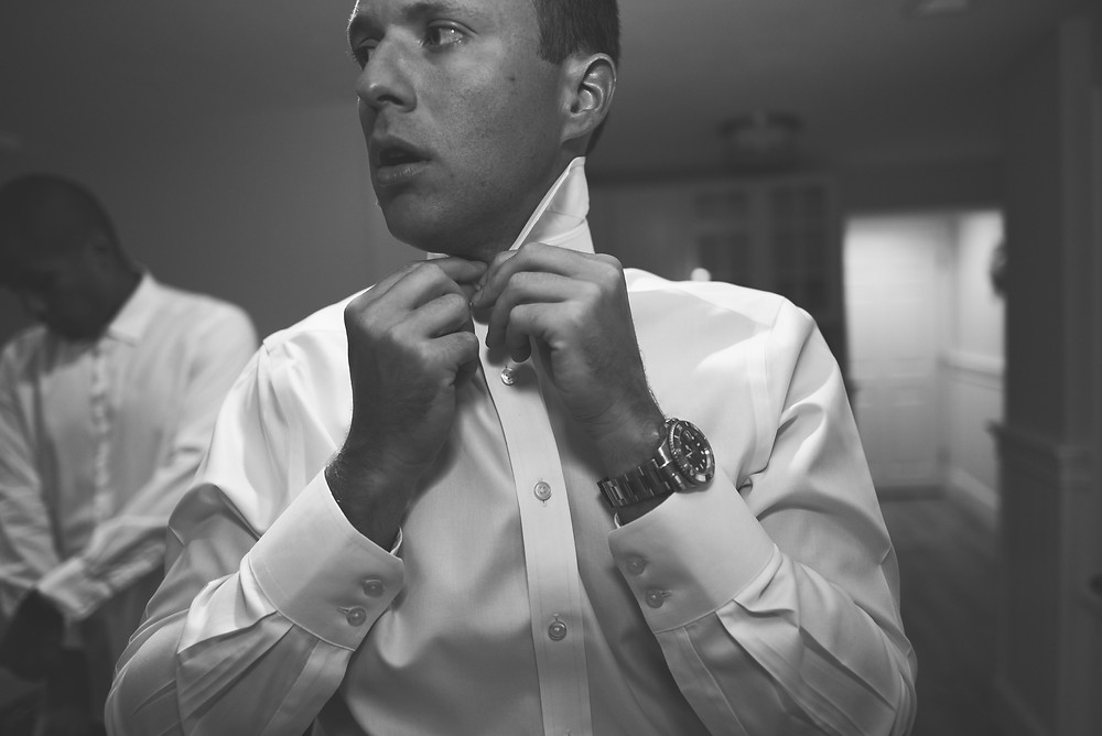 black and white photo of groom buttoning collar