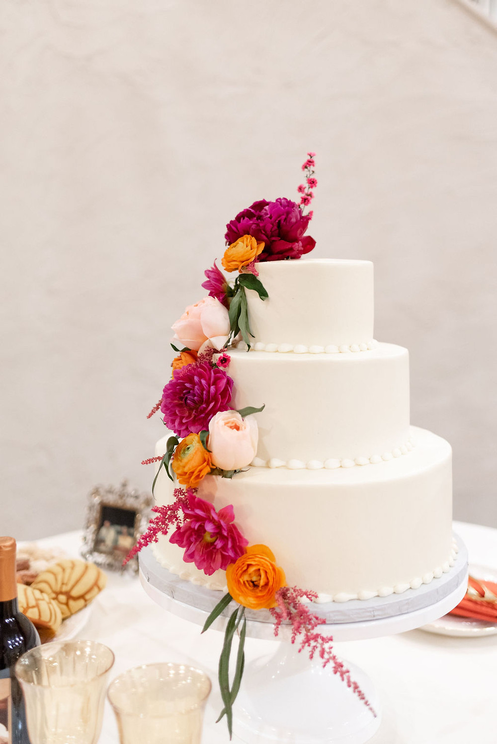 white wedding cake with pink and orange flowers