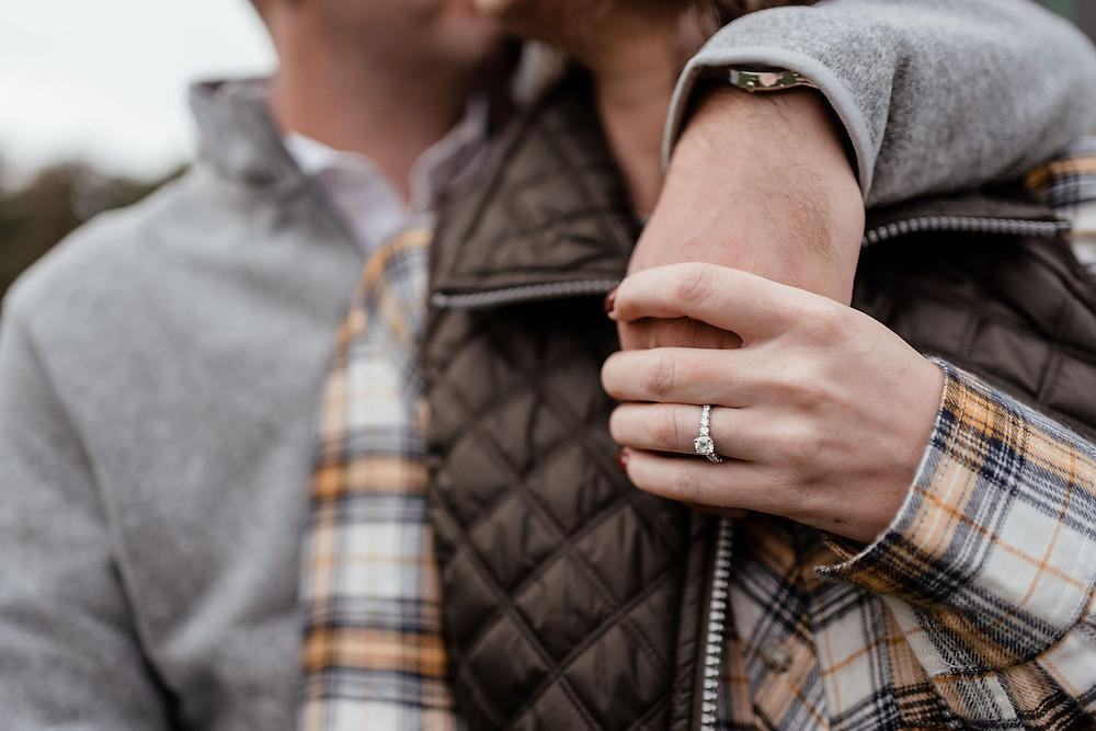 close up photo of engagement ring on girls hand. she is holding guys hand