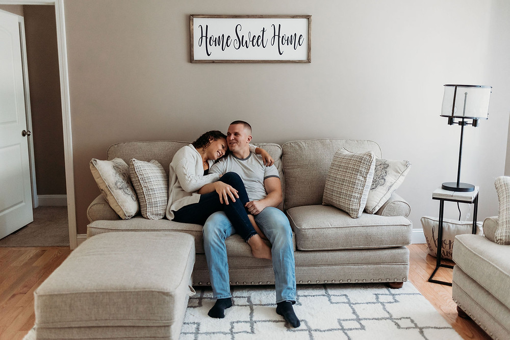 in home engagement session couple sits on couch cuddly