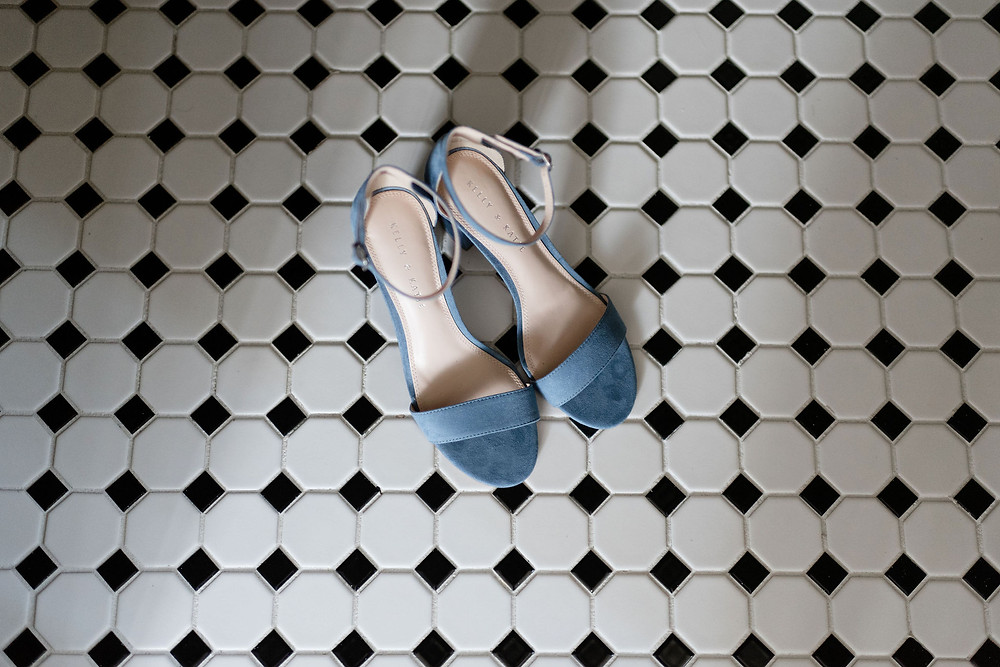 blue wedding shoes on black and white checkered tiled floor