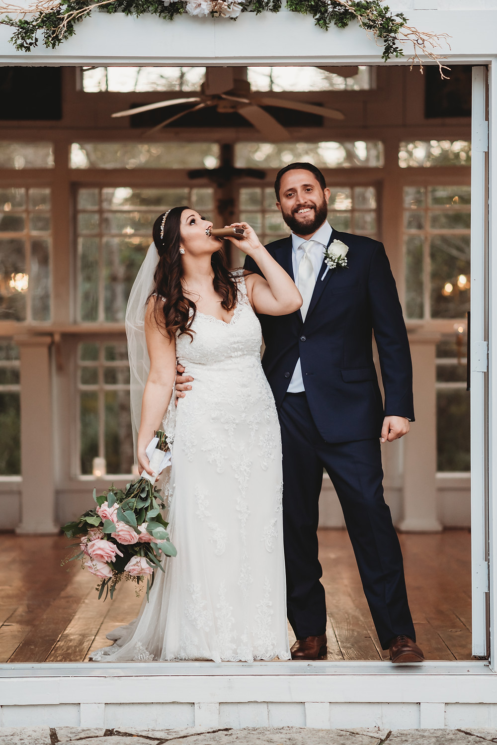 bride drinking out of a flask during newlywed photos