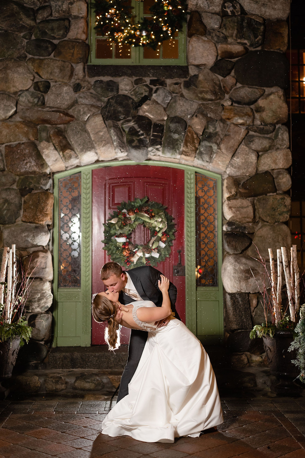 bride and groom dip and kiss wedding pose in front of the red door at willowdale estate