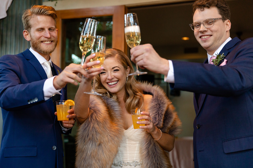 couple and best man cheer-sing with champagne flutes