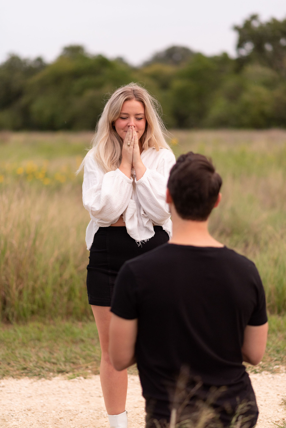 girl's reaction to boyfriend proposing. her hands are in front of her face shielding her mouth