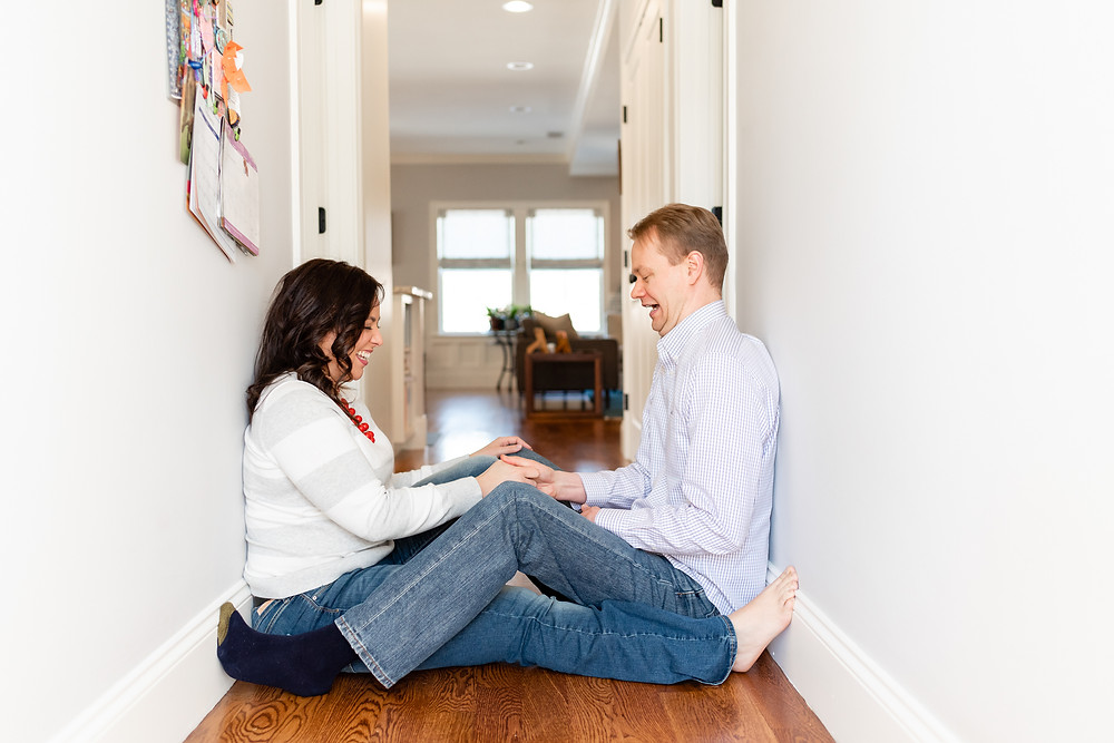 engagement in home session with couple sitting in hallway having a thumb wrestling war